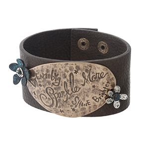 """Dark brown, faux leather snap bracelet with a gold tone focal stamped with """"Dream Big, Sparkle More, Shine Brighter."""" Approximately 1.5"""" in width."""