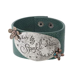 "Teal, faux leather snap bracelet with a silver tone focal stamped with ""Dream Big, Sparkle More, Shine Brighter."" Approximately 1.5"" in width."