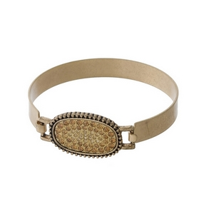 Matte gold tone bangle with a topaz pave rhinestone oval focal.
