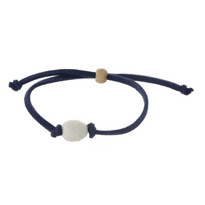 Navy blue faux suede cord adjustable bracelet with a freshwater pearl bead.