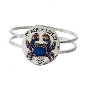 "Silver tone hinged bangle bracelet featuring a circle focal stamped with ""Beach Life."""
