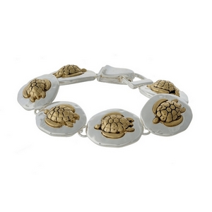 Silver tone magnetic bracelet featuring gold tone turtles.