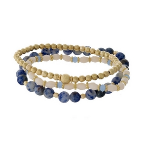 Three piece stretch bracelet set featuring sodalite natural stone beads, gold tone beads, and ivory faceted beads.