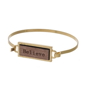 "Gold tone bangle bracelet featuring a wooden focal stamped with ""Believe."""