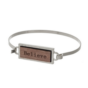 "Silver tone bangle bracelet featuring a wooden focal stamped with ""Believe."""