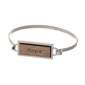 "Silver tone bangle bracelet featuring a wooden focal stamped with ""Hope."""