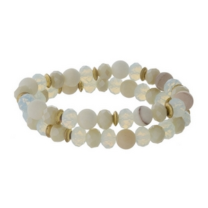 Ivory natural stone and faceted bead stretch bracelet set with gold tone accents.