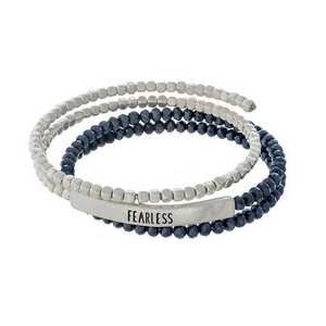 """Navy blue and silver tone beaded coil bracelet featuring a bar stamped with """"Fearless."""""""