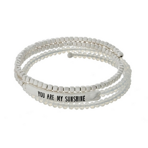 """White opal and silver tone beaded coil bracelet featuring a bar stamped with """"You are my sunshine."""""""