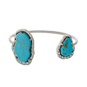 Burnished silver tone cuff bracelet displaying two turquoise natural stones accented with clear rhinestones.