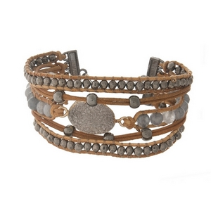Brown leather cord bracelet featuring a faux gray druzy stone, gray beads, and a toggle closure.