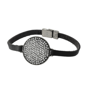 Black leather bracelet with a burnished silver tone and clear rhinestone circle, and a magnetic closure.