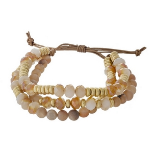Three row, beaded pull-tie bracelet featuring peach druzy and champagne beads with gold tone accents. Handmade in the USA.