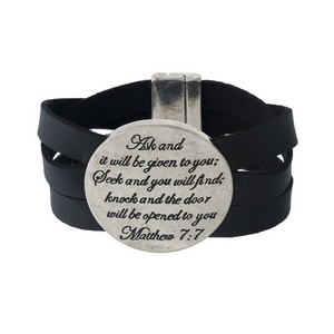 "Black faux leather magnetic bracelet featuring a silver tone circle stamped with ""Ask and it will be given to you; Seek and you will find; Knock and the door will be opened to you."""
