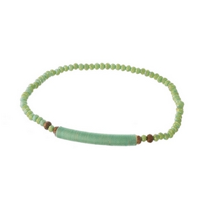 Dainty light green beaded stretch bracelet with a thread wrap focal.