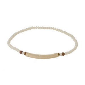Dainty ivory beaded stretch bracelet with a thread wrap focal.