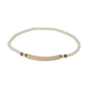 Dainty ivory beaded stretch bracelet with a thread wrap focal.