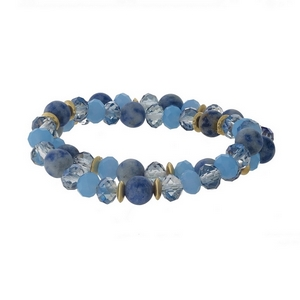 Blue natural stone and faceted bead stretch bracelet set with gold tone accents.