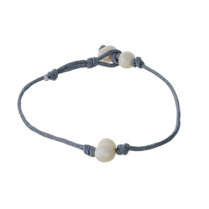 Gray cord bracelet with a freshwater pearl and a button closure.