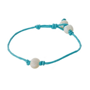 Mint green cord bracelet with a freshwater pearl and a button closure.