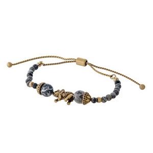 Gray beaded pull-tie bracelet with a gold tone elephant focal.