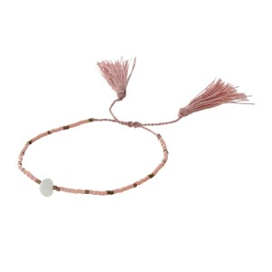 Mauve pull-tie cord bracelet with peach beads and tassel accents.