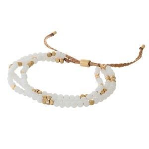 Brown cord, pull-tie bracelet featuring three rows of white natural stone beads.