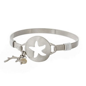 Silver tone bangle bracelet with a starfish cutout.