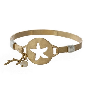 Gold tone bangle bracelet with a starfish cutout.