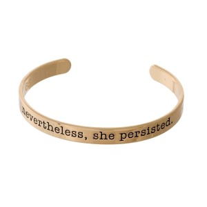 "Gold tone cuff bracelet stamped with ""nevertheless, she persisted."""