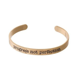 "Gold tone cuff bracelet stamped with ""progress, not perfection."""