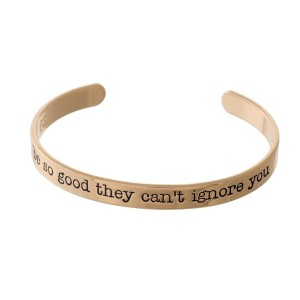 "Gold tone cuff bracelet stamped with ""be so good they can't ignore you."""