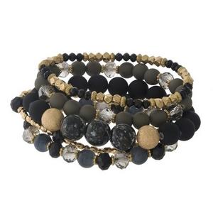 Four piece, black and gold tone beaded stretch bracelet set.