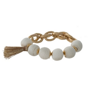 Gold tone stretch bracelet with ivory thread wrapped ball beads and a tassel accent.
