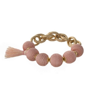 Gold tone stretch bracelet with peach thread wrapped ball beads and a tassel accent.