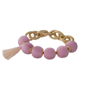 Gold tone stretch bracelet with pale pink thread wrapped ball beads and a tassel accent.