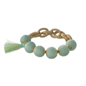Gold tone stretch bracelet with mint green thread wrapped ball beads and a tassel accent.