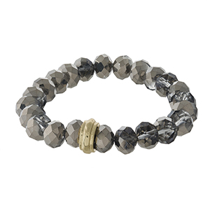 Gray beaded stretch bracelet with a gold tone accent.