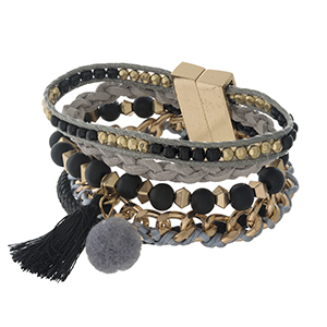 Gold tone magnetic bracelet with black, gray, tassel and pom pom accents.