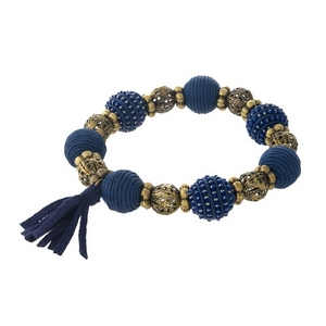 Navy blue thread wrapped and burnished gold tone, stretch bracelet with a tassel accent.