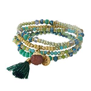 Green, teal and gold tone beaded four piece bracelet set with a tassel accent.