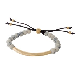 Howlite, natural stone beaded pull-tie bracelet with a hammered gold tone bar.