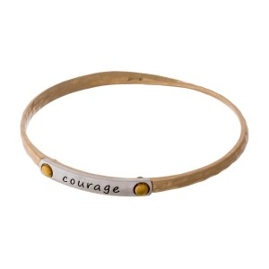 "Gold tone bangle bracelet with a two tone bar, stamped with ""Courage."""