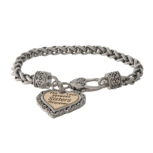"""Silver tone bracelet with a two tone heart charm stamped with """"The love between Sisters is forever."""""""