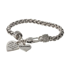 "Silver tone bracelet with two heart charms stamped with ""The heart that loves is always young"" and ""Grandma."""