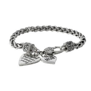 "Silver tone bracelet with two heart charms stamped with ""The heart that loves is always young"" and ""Mom."""