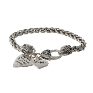 "Silver tone bracelet with two heart charms stamped with ""The heart that loves is always young"" and ""Mimi."""