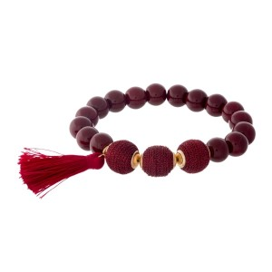 Burgundy beaded stretch bracelet with thread wrapped beads and a tassel accent.