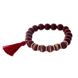 Burgundy beaded stretch bracelet with wooden beads and a tassel accent.
