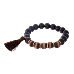 Brown beaded stretch bracelet with wooden beads and a tassel accent.